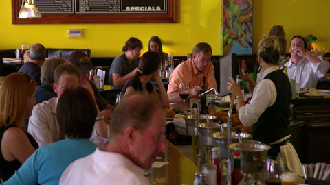 Bar tender serves people seated at the bar Live Action