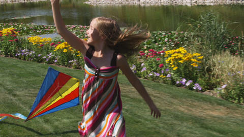 Girl playing with a kite in beautiful gardens Footage