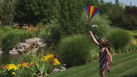 Clip of a girl playing with a kite in beautiful gardens Footage