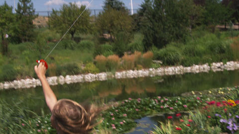 Slow motion clip of a girl playing with a kite in beautiful gardens Footage