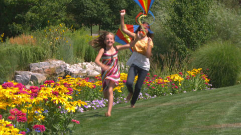 Two girls play with kites in beautiful gardens Footage