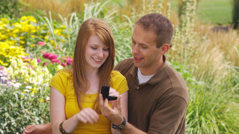 Young man proposing to a young woman in a beautiful garden Live Action