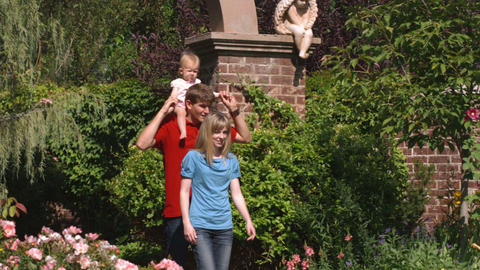 Family walking through beautiful gardens in slow motion Footage
