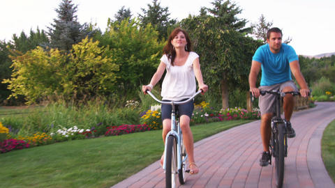 Young couple riding bikes through a beautiful garden Footage