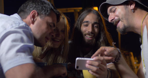 Friends laughing at photos on mobile phone Footage