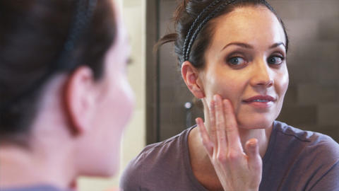 Close-up of a mirror as a woman applies face cream Footage