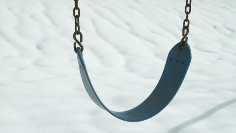 Single empty swing on a snowy day Footage