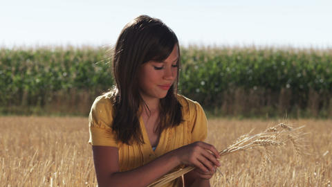 Happy woman in a wheat field holding strands of wheat Footage