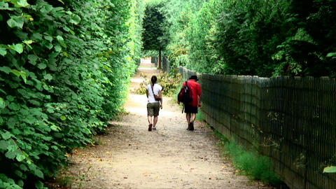 Man and woman walking down a trail through greenery in Paris, France Footage