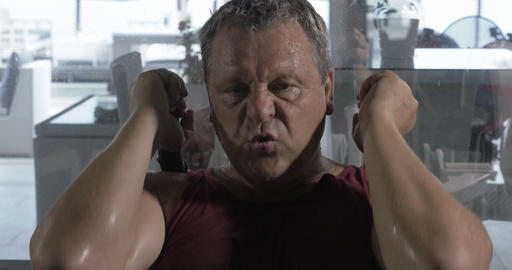 Man getting tired and sweaty training on fitness machine Footage