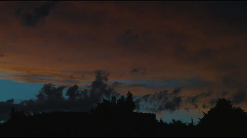 A sunset lights up the clouds in the sky Footage