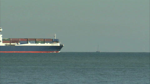 Cargo ship coming into view on the ocean Live Action