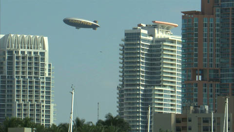 Goodyear blimp appearing from behind a Miami hotel Live Action