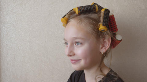 Portrait smiling young girl with curlers on hair on copy space background Footage