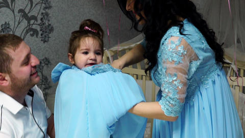 Parents dress their daughter in a close-up dress Footage