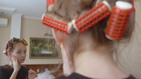 Teenager girl with curlers on hair applying tone cream front mirror in bedroom GIF