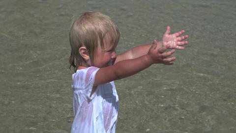 Beautiful little girl walks along the seashore. Little girl in a white dress on Footage