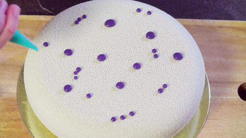 Hands decorating the cake with silver droplets Footage