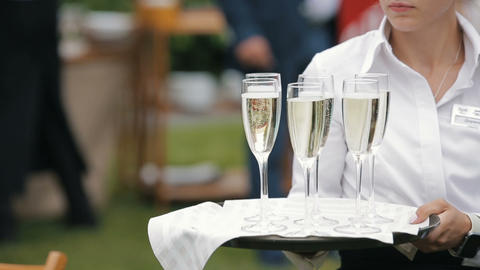 Young waitress carrying a tray with six glasses of champagne Footage