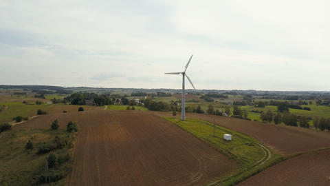 Aerial view of single wind turbine rotating fast. Summer countryside with Footage