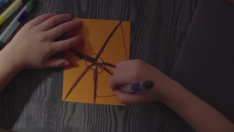 Girl's hands drawing spider web on a card. Preparing for the celebration of Live Action