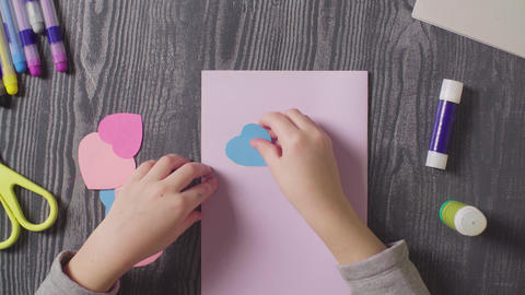 Girl's hands glueing a card. Valentine's Day Live Action