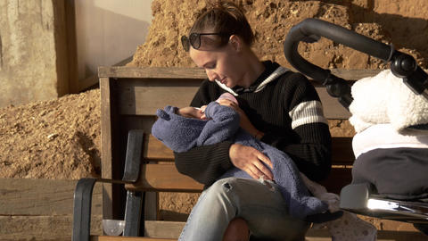 Positive and smiling mama feeding baby outdoor on a bench having rest Footage