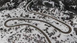 Snowy mountain serpentine by the sea ビデオ