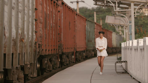 Woman walking near train rail on train station. Beauty, freedom, summer travel Footage