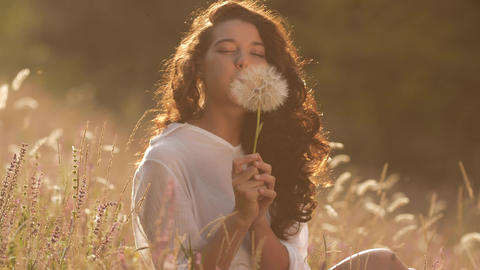 Beautiful young woman blows dandelion in a wheat field in the summer sunset Live Action