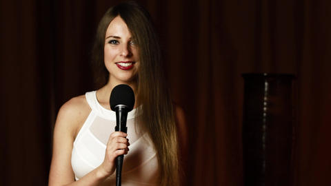 Pretty woman in white dress holds microphone and sings with spectacular smile ビデオ