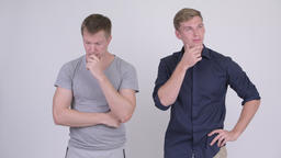 Scandinavian man thinking seriously with businessman thinking happily Footage