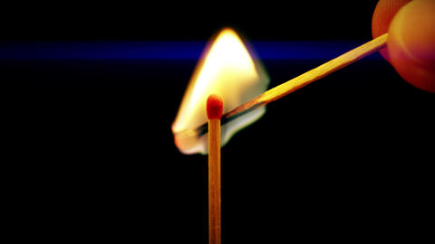 Man lighting a match with another match in the dark, close-up shot Live Action