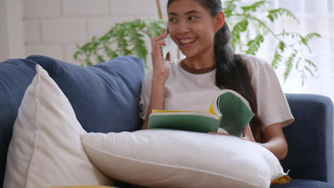 Asian woman reading book and cell phone on sofa in living room at home Footage