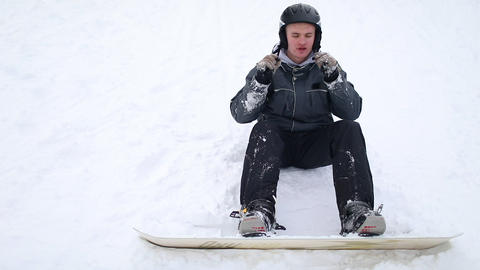 Snowboarder Wearing Helmet for safety, Sitting on Snow Live Action