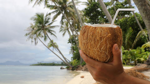 Coconut water on paradise beach - vacation woman holding drinking coconut water Footage