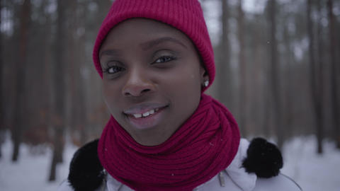 Portrait cute smilling african american girl wearing a red hat and a red scarf Live Action