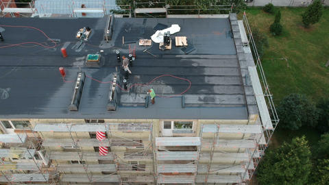 Workers roofers repair flat house roof in city, aerial Live Action