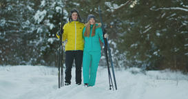Side view portrait of active young couple carrying skis chatting on the way back Footage
