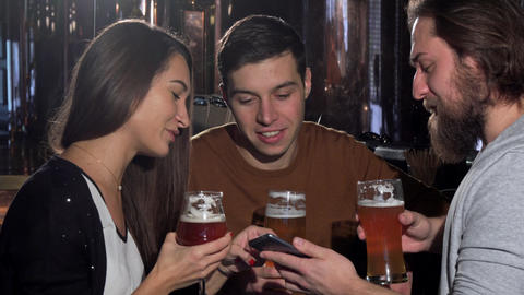 Group of friends having fun at beer pub, using smart phone together Live Action