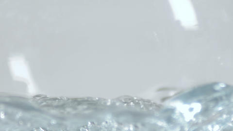 Extreme close-up of water filling a clear glass container Footage