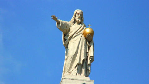Statue of a man with a golden religious emblem in his hand Live Action