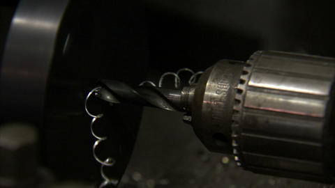 Close up of a drill that is stationary while metal spins around it Live Action
