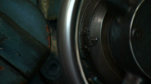 Close up of a metal wheel being turned by hands Live Action