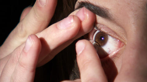 Extreme close up of a woman putting a contact in her eye Footage