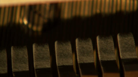 Close up shot of piano hammers striking the piano's strings Footage