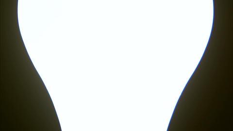 Close up pan down a lit lightbulb Live Action