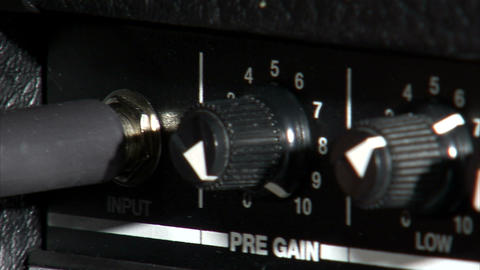 Close up of a cord being plugged into a guitar amp Footage