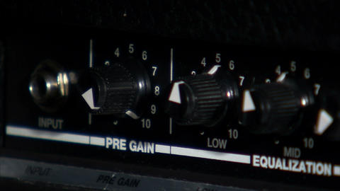 Close up of hands turning guitar amp knobs Live Action