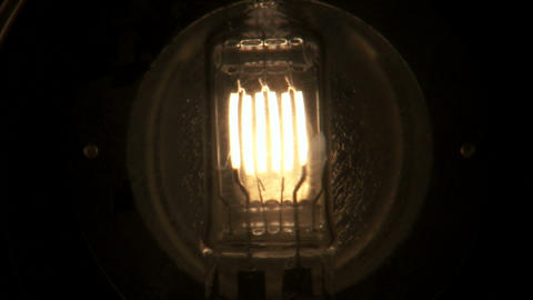 Close up of a light bulb with several filaments fading on then off Footage